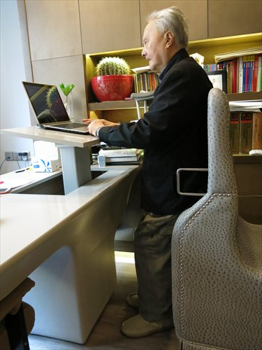 Wang Zhichong using a customized chair that helps him stand at his desk
